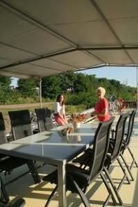 tafel met zwarter dekstoelen onder een luifel. Een grootmoeder en kleindochter genieten verderop van het zonnedek