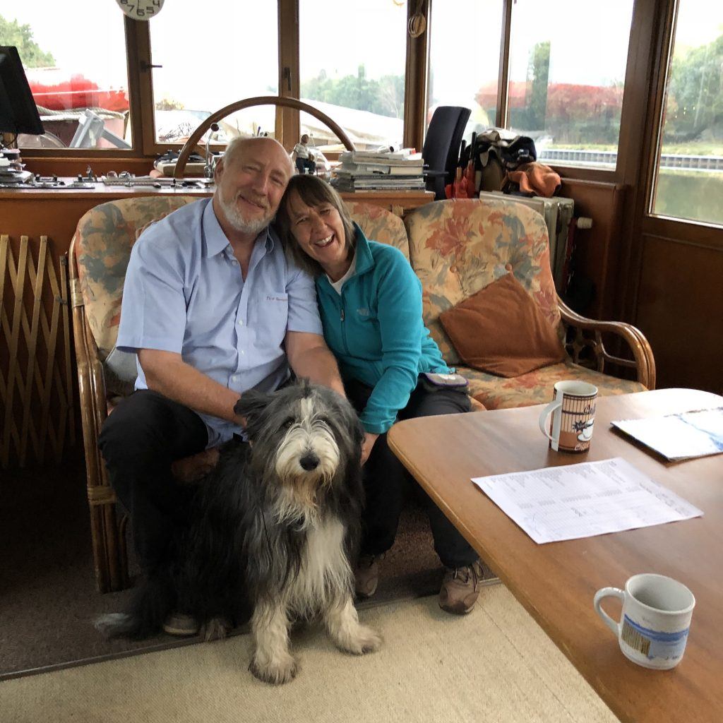 Het stuurhuis met op de bank de bemanning van De 4 Vaargetijden: Maurits en Olga naast elkaar met scheepshond Noty aan hun voeten.