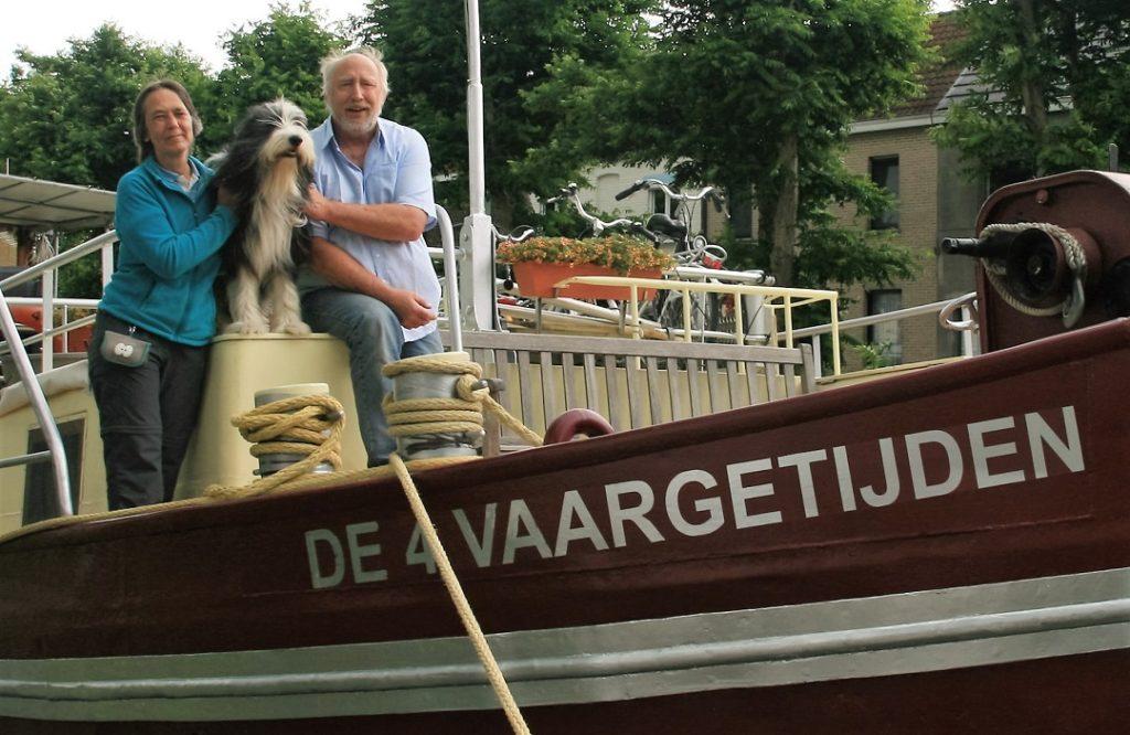 De boeg van het schip De 4 Vaargetijden met naast elkaar haar bemanning: Olga en Maurits. Tussen hen in zit scheepshond Noty op de bakskist.